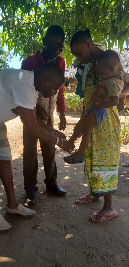 Vengono donate delle scarpe ad un bimbo in braccio alla madre.